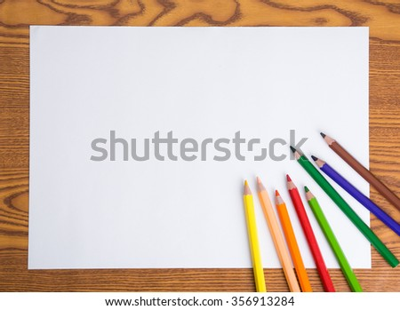 Blank white paper and color pencil on wooden table