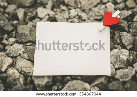 Blank white paper and red clip paper heart on the clothesline with many stone nature background.Designer concept.vintage or retro tone. - stock photo