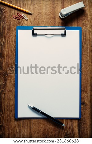 Blank white paper on a clipboard surrounded by a pen pencil and eraser ready to take notes at a meeting or in the classroom at school, overhead view on a wooden desk - stock photo