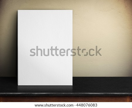 Blank White paper poster on black marble table at yellow concrete wall,Template mock up for adding your design and leave space beside frame for adding more text.