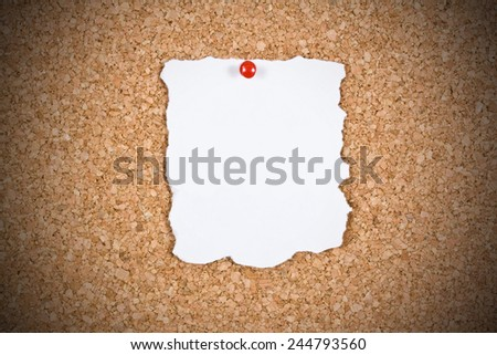 Blank white paper ragged around the edges pinned on cork billboard - stock photo