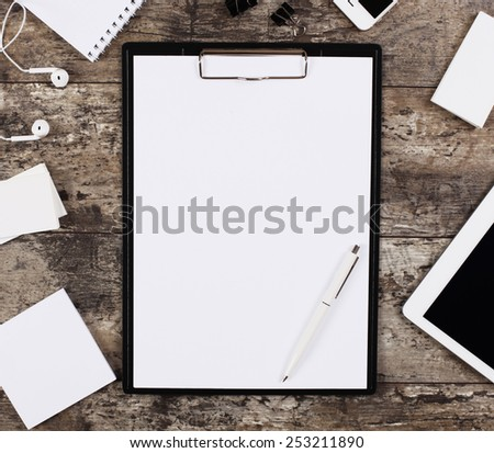 Blank white paper sheet in a clip folder surrounded by office supplies, mobile phone, touchpad  - stock photo