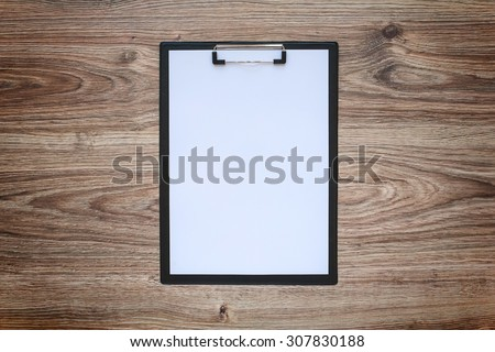 Blank white paper sheet in a clipboard on wooden table. Template. - stock photo