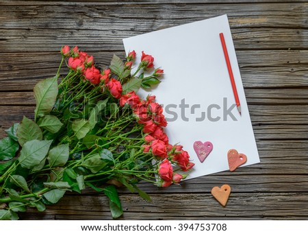 Blank white paper with copy space on top of wooden surface beside bundle of roses, Valentines Day hearts and pencil - stock photo