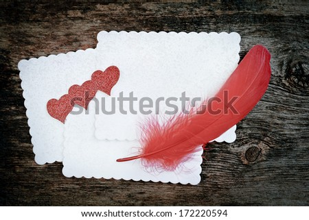 Blank white paper with red feather and hearts on it.  Wooden background.