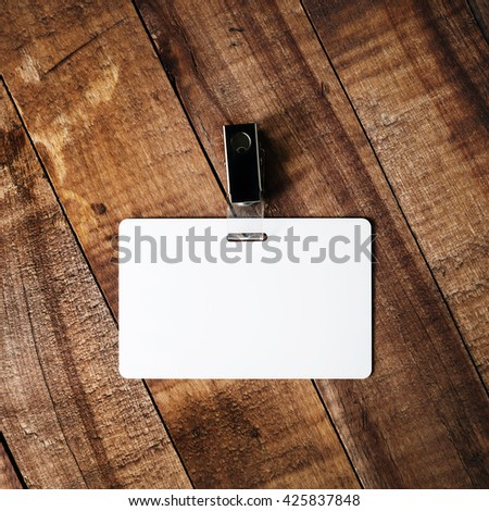 Blank white plastic badge. Template for ID. Blank badge on vintage wooden table background. Mock-up for branding identity for designers. Top view. - stock photo