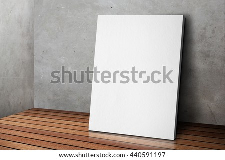 Blank white poster frame leaning at grunge grey concrete wall and wood floor, Mock up template for adding your design.