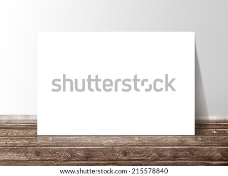 Blank white rectangle paper template banner on the wooden floor against the wall - stock photo