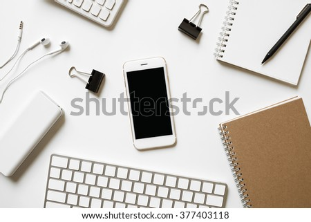Blank white smartphone, office supplies with school documents on office desk top view