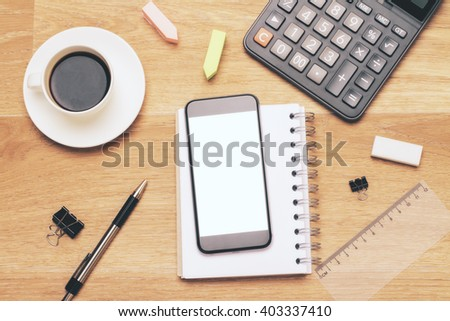 Blank white smartphone on wooden table with calculator and other office tools. Mock up