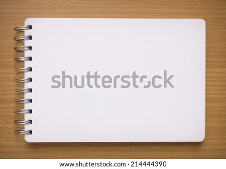 blank white spiral notebook on wood background - stock photo