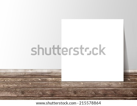 Blank white square paper template banner on the wooden floor against the wall