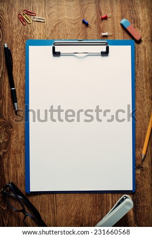 Blank white standard A4 paper sheet in a blue clip folder surrounded by office supplies as pen, pencil, eraser, stapler, clips and pins, on a wooden table, high-angle close-up - stock photo