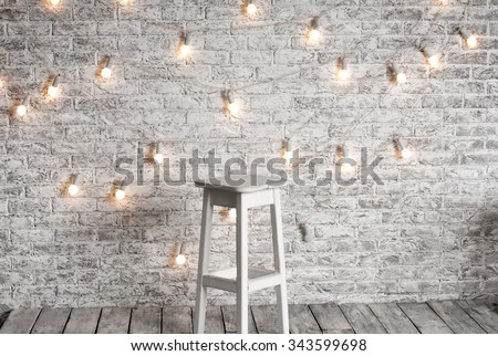 Blank white stool against the backdrop of a brick wall with a garland of light bulbs - stock photo