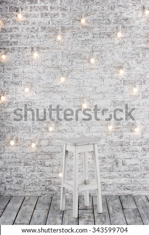 Blank white stool against the backdrop of a brick wall with a garland of light bulbs