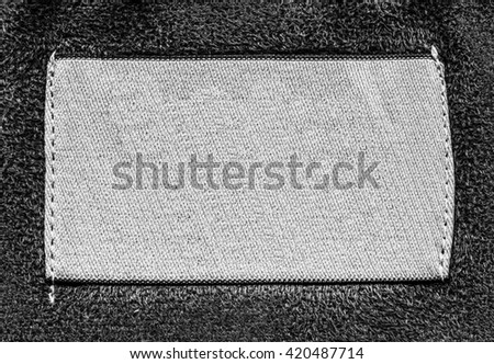 blank white textile label on gray textile background