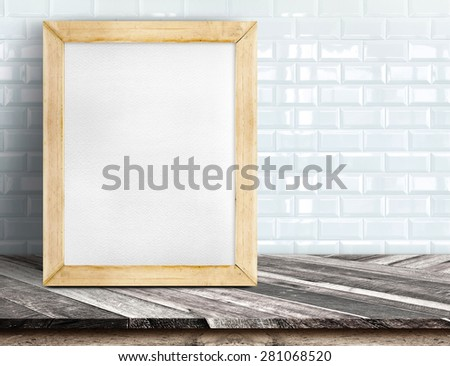 Blank whiteboard wood frame on tropical wooden table at white tile wall,Template mock up for adding your design and leave space beside frame for adding more text - stock photo