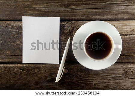 Blank with pen and cup of coffee on wooden table