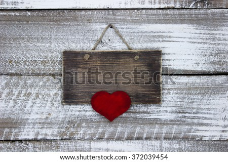 Blank wood sign with large red heart hanging on antique rustic white wooden background; Valentine's Day, family and love concept - stock photo