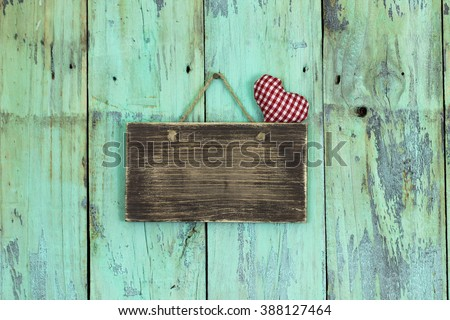 Blank wood sign with rope heart hanging on antique rustic mint green wooden background; Valentine's Day and love concept - stock photo