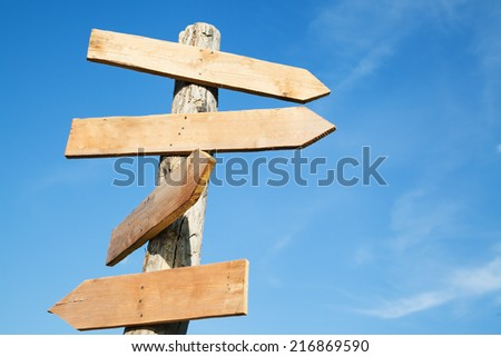 Blank wooden arrow shape signs against blue sky