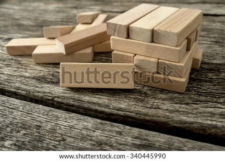 Blank wooden block leaning on a structure made of many other blocks with several of them still lying scattered on a textured rustic wooden desk. Conceptual of leisure game or start up business. - stock photo