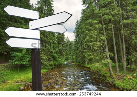 Blank wooden guidepost in mountain scenery - stock photo