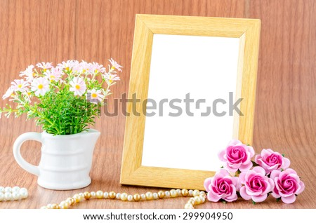 Blank wooden photo frame and pink rose on wooden background. Save clipping path. - stock photo