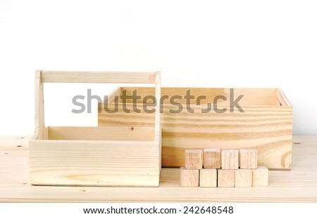 Blank wooden storage boxes and wooden cubes on table background, display template - stock photo