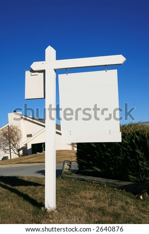 Blank wooden white real estate sign in yard - stock photo