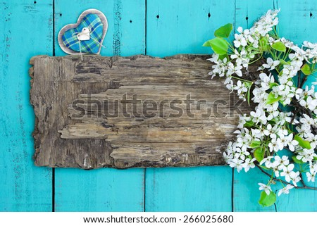 Blank worn wooden sign with spring tree blossoms border and fabric heart hanging on antique teal blue wood background - stock photo