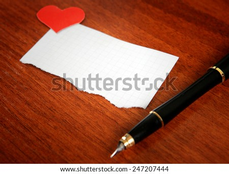 Blank Writing Pad with Heart Shapes and Pen on The Table - stock photo