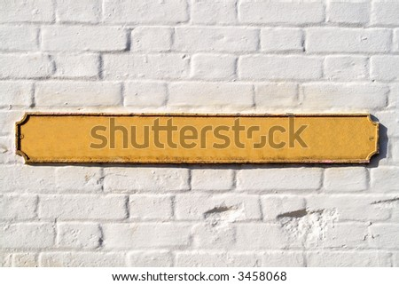 Blank yellow British street sign on a white wall. - stock photo
