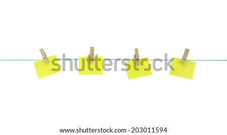 Blank yellow note papers hanging with wood pegs on clothesline. - stock photo