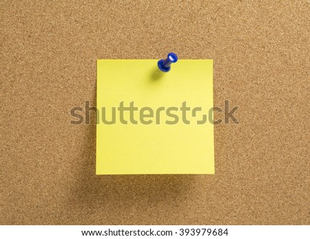 Blank yellow notepaper with blue push pin on a corkboard