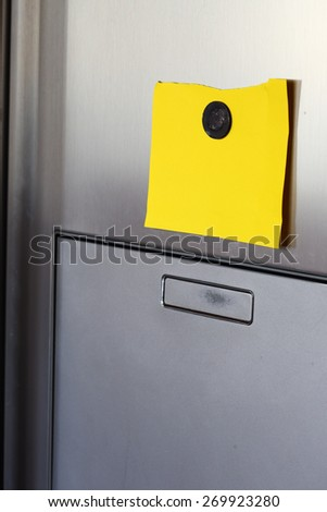 Blank yellow  paper and magnet on refrigerator door. - stock photo