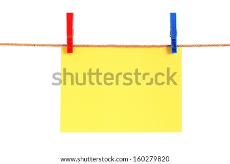 Blank yellow paper hanging on rope with clothespins. Isolated with clipping path