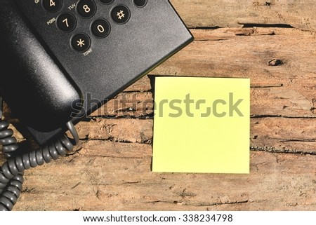 blank yellow paper on wood table with black telephone - stock photo
