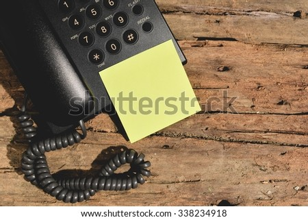 blank yellow paper on wood table with black telephone