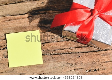 blank yellow paper on wood table with gift box - stock photo