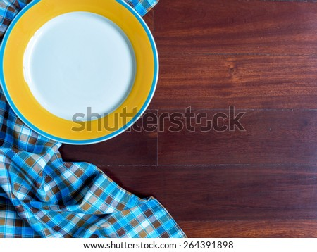Blank yellow plate on checked tablecloth over wooden table background - stock photo