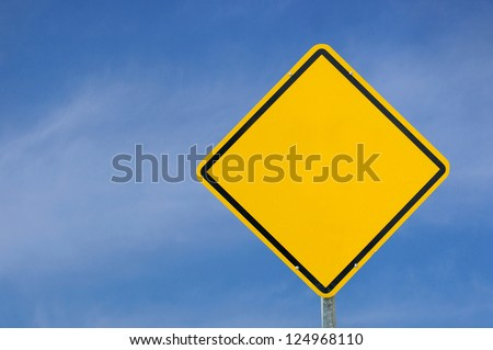 Blank yellow sign frame against blue sky.