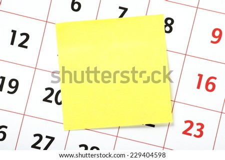 Blank yellow sticky note with copy space stuck on a calendar as a reminder - stock photo