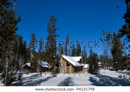 Blanked with snow the winter has surrounded this little log cabin