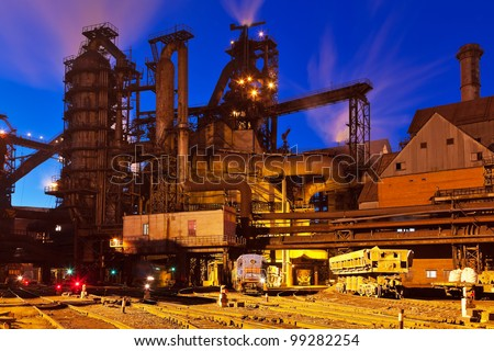 Blast furnace equipment of the metallurgical plant at night - stock photo