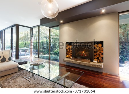 Blazing fire in living room of luxury architect designed Australian house - stock photo