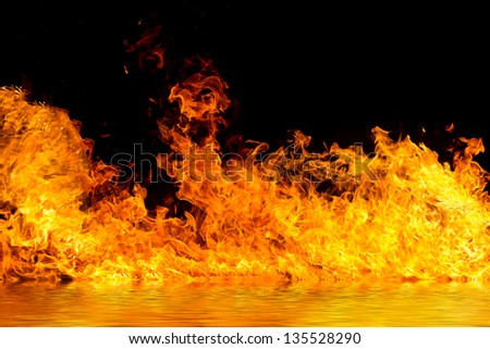 Blazing flames with water reflections over black background
