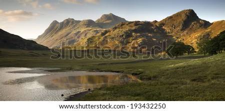 Blea Tarn reflects a beautiful sunset on the Langdale Pikes in the English Lake District.  - stock photo