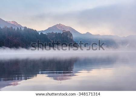 Bled castle covered in fog with the mystic lake below - stock photo