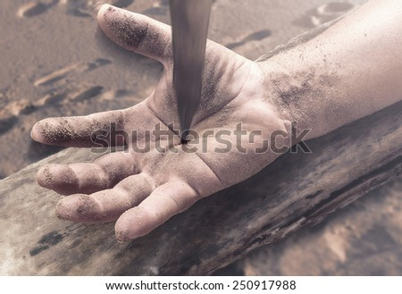 Bleeding hand with nail in it on wood. - stock photo